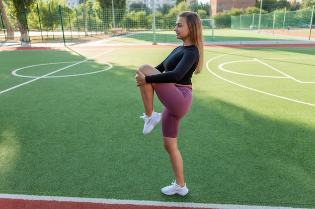 Jovem mulher atraente em roupas esportivas, fazendo aquecimento pré-treinamento, alongamento de pernas no estádio. conceito de estilo de vida saudável. treinamento ao ar livre