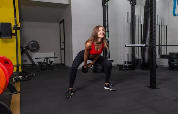 Jovem mulher atraente em roupas esportivas pratica exercícios kettlebell pesados no ginásio moderno. treinamento de pesos livres