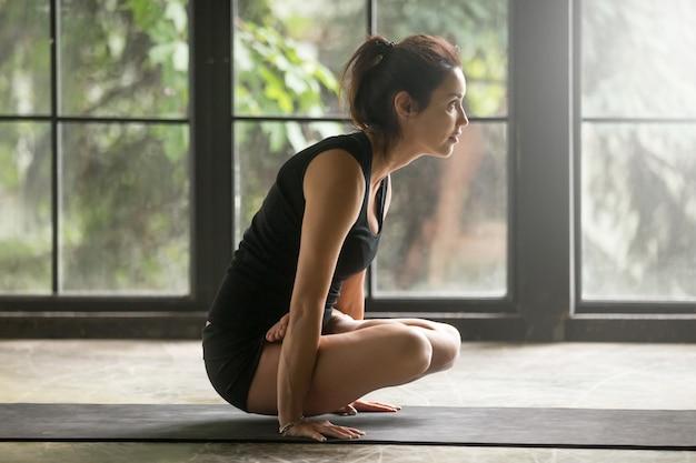 Jovem mulher atraente em tolasana pose, fundo de estúdio