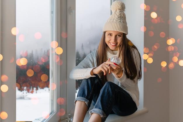Jovem mulher atraente em um elegante suéter branco de malha, lenço e chapéu sentada em casa no parapeito da janela no natal segurando a decoração do presente da bola de neve de vidro, vista da floresta de inverno, luzes bokeh