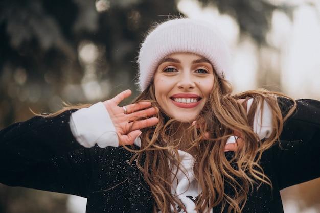 Jovem mulher atraente em um parque de inverno com um chapéu fofo