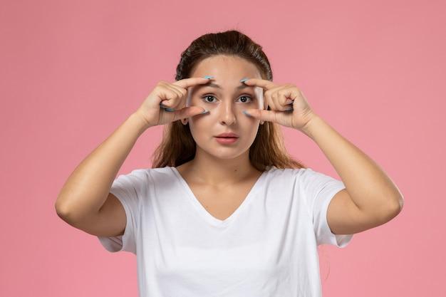 Jovem mulher atraente em uma camiseta branca, de frente para a frente, mostrando os olhos no fundo rosa