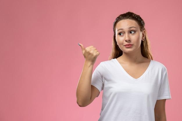 Jovem mulher atraente em uma camiseta branca posando com um gesto de apontar no fundo rosa.