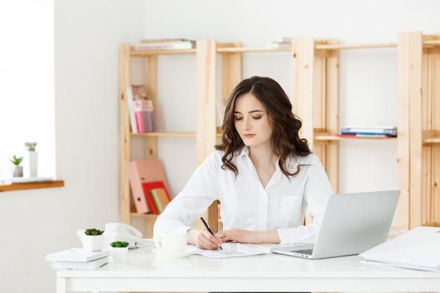 Jovem mulher atraente em uma mesa de escritório moderna, trabalhando com o laptop e pensando em alguma coisa.