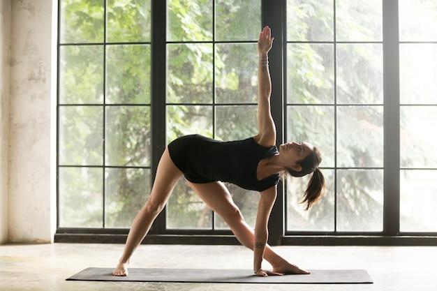 Jovem mulher atraente em utthita trikonasana pose