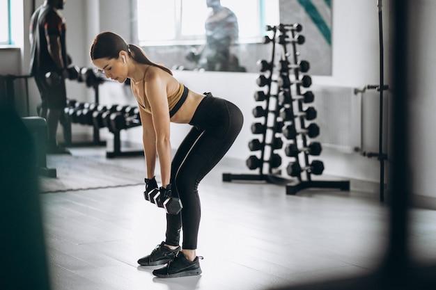 Jovem mulher atraente, exercitar-se com halteres na academia