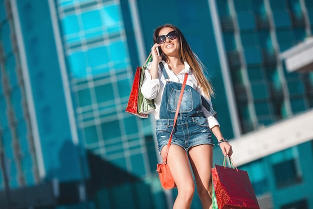 Jovem mulher atraente, falando em um telefone celular e carregando sacolas de compras