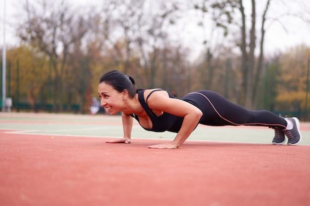 Jovem mulher atraente faz prancha de treinamento ao ar livre