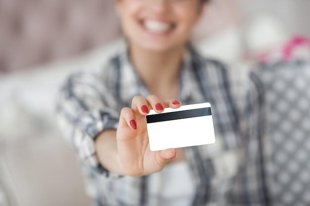 Jovem mulher atraente fazendo compras online em casa