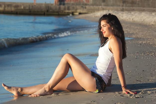 Jovem mulher atraente fazendo exercícios de ioga na praia. garota fazendo pilates na costa do oceano. exercícios de fitness ao ar livre ao ar livre.