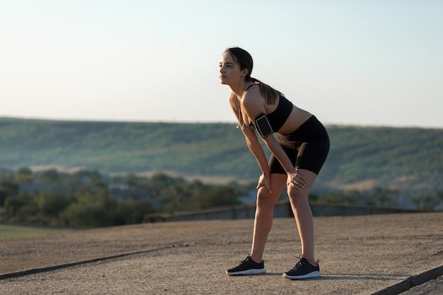 Jovem mulher atraente fazendo exercícios malhando ao ar livre.