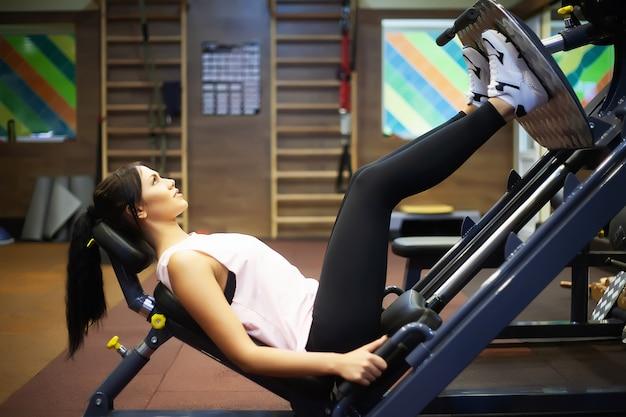 Jovem mulher atraente fazendo exercícios no ginásio de fitness.