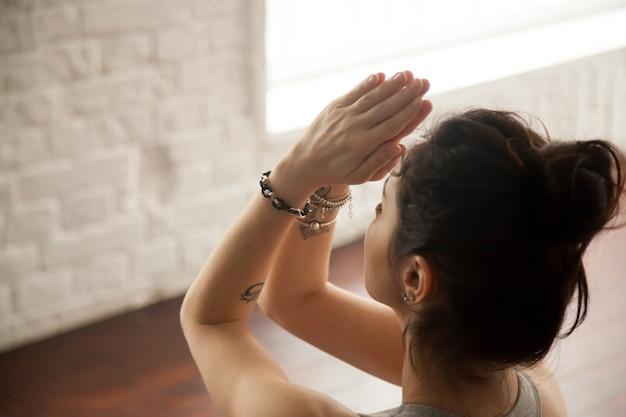 Jovem mulher atraente fazendo gesto namaste