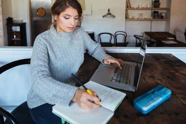 Jovem mulher atraente fazendo sua lição de casa em um café
