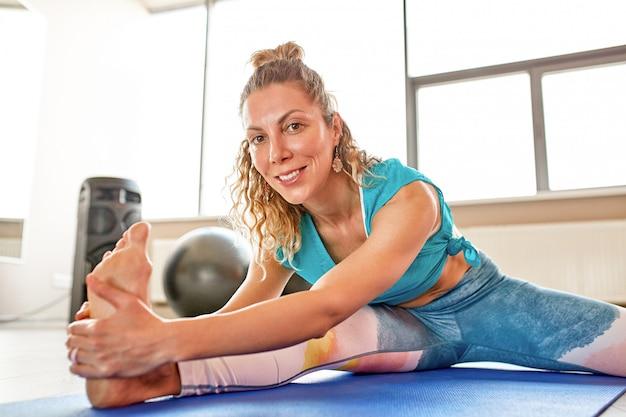 Jovem mulher atraente fazendo yoga na sala de fitness. ambiente de luz natural.