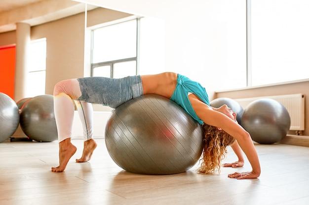 Jovem mulher atraente fazendo yoga na sala de fitness.