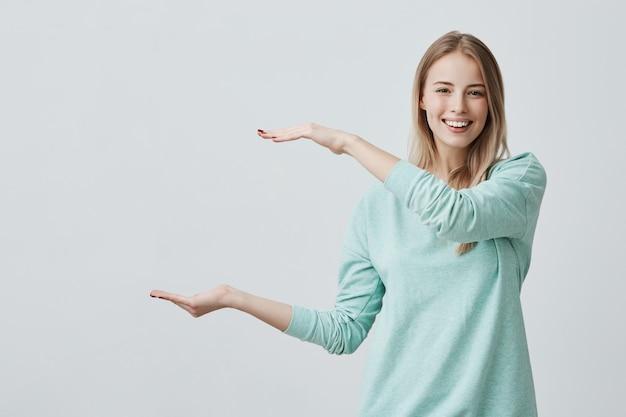 Jovem mulher atraente feliz na camisola azul clara, mostrando algo grande com as mãos