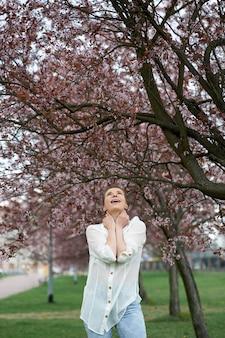 Jovem mulher atraente feliz no fundo da florescência de sakura.