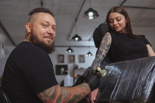 Jovem mulher atraente, ficando nova tatuagem por tatuador profissional