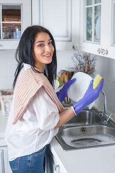 Jovem mulher atraente lavando o prato dentro de casa.