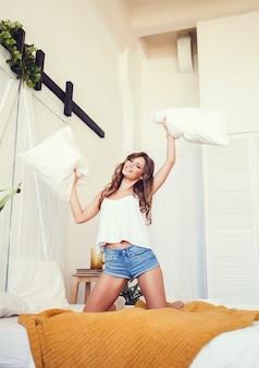 Jovem mulher atraente, morena alegre com almofadas