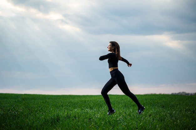 Jovem mulher atraente morena de pé na natureza, vestindo legging preta e um top preto. dia de verão, grama verde. corpo atlético e estilo de vida saudável.