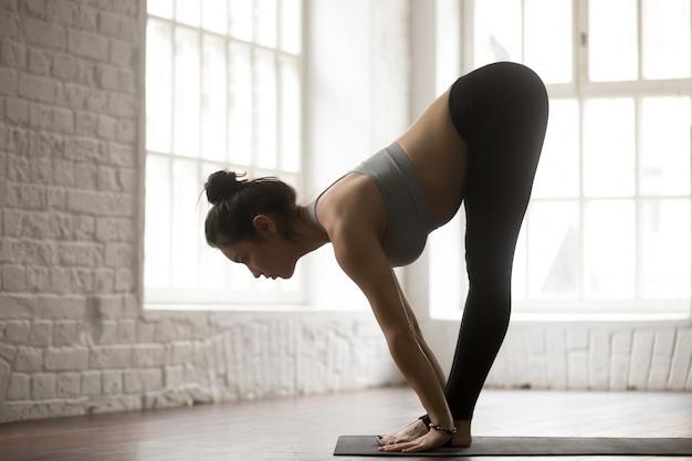 Jovem mulher atraente na cabeça de joelhos pose, estúdio branco