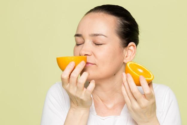 Jovem mulher atraente na camisa branca, cheirando laranjas silced