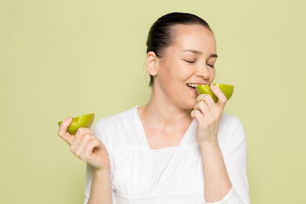 Jovem mulher atraente na camisa branca, segurando e comendo maçãs verdes em fatias