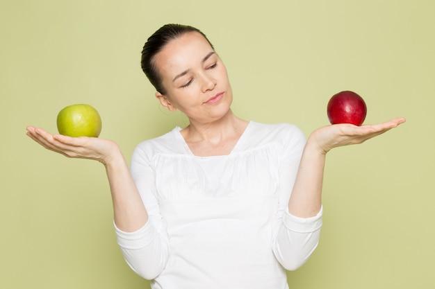 Jovem mulher atraente na camisa branca segurando maçãs verdes e vermelhas