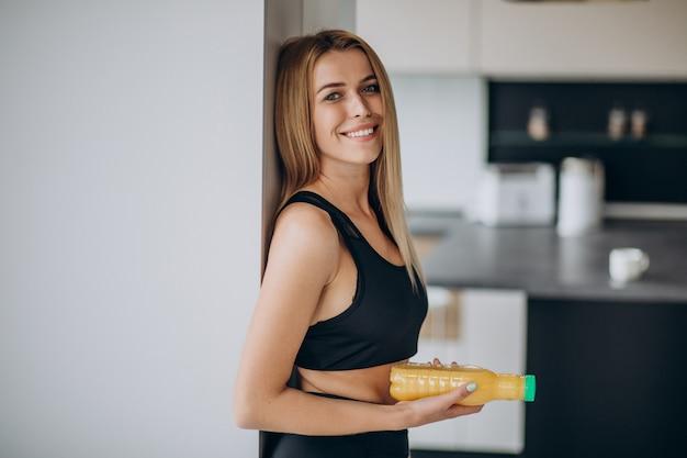 Jovem mulher atraente na cozinha com suco