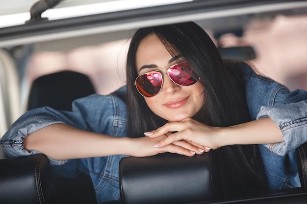 Jovem mulher atraente no carro. mulher dirige um automóvel. feche acima do retrato da mulher bonita ao ar livre. senhora urbana.