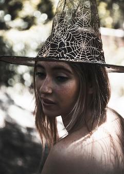 Jovem mulher atraente no chapéu de bruxa na floresta murcha