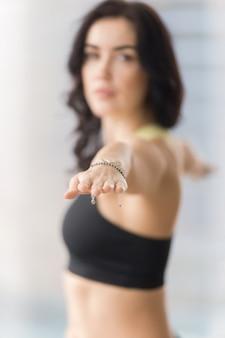 Jovem mulher atraente no guerreiro dois, closeup de suas mãos