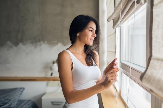 Jovem mulher atraente olhando pela janela no quarto