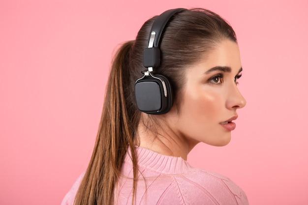 Jovem mulher atraente ouvindo música em fones de ouvido sem fio, vestindo um suéter rosa, sorrindo, feliz humor positivo, posando em fundo rosa