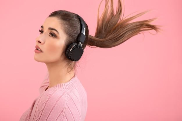 Jovem mulher atraente ouvindo música em fones de ouvido sem fio, vestindo um suéter rosa, sorrindo, feliz humor positivo, posando em um fundo rosa isolado balançando um rabo de cabelo comprido