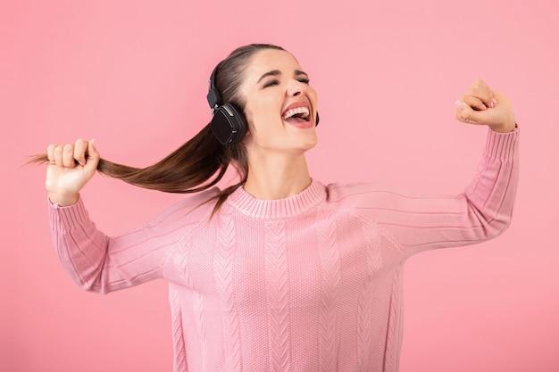 Jovem mulher atraente ouvindo música em fones de ouvido sem fio, vestindo um suéter rosa