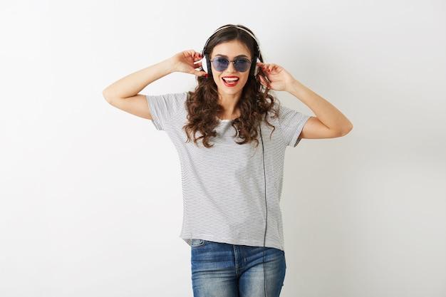 Jovem mulher atraente ouvindo música em fones de ouvido, usando óculos escuros, cabelo encaracolado, humor lúdico, isolado no fundo branco, camiseta, estilo casual hipster, emoção positiva feliz, emocional