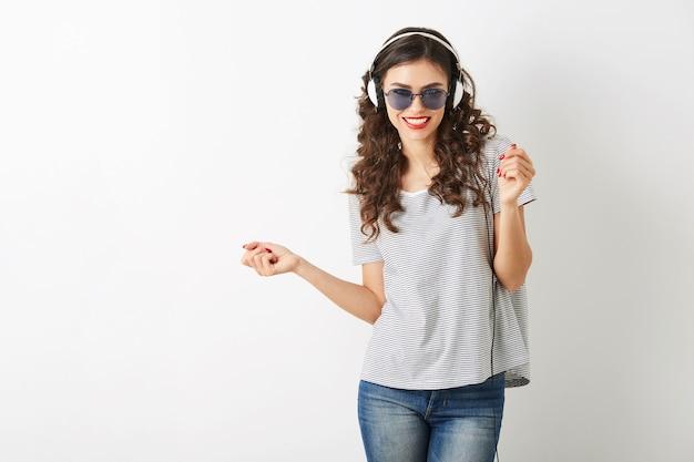Jovem mulher atraente ouvindo música em fones de ouvido, usando óculos escuros, isolado no fundo branco,