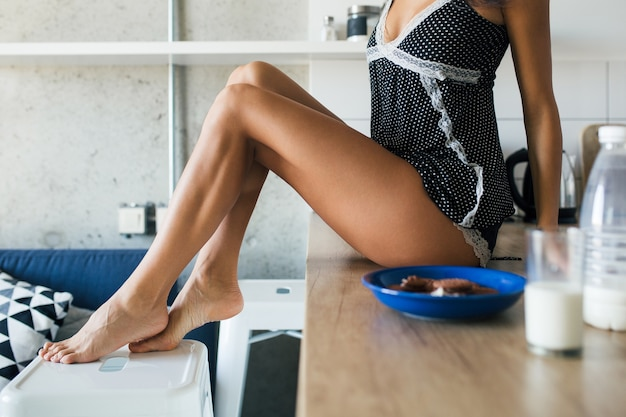 Jovem mulher atraente pela manhã na cozinha, pernas longas sexy