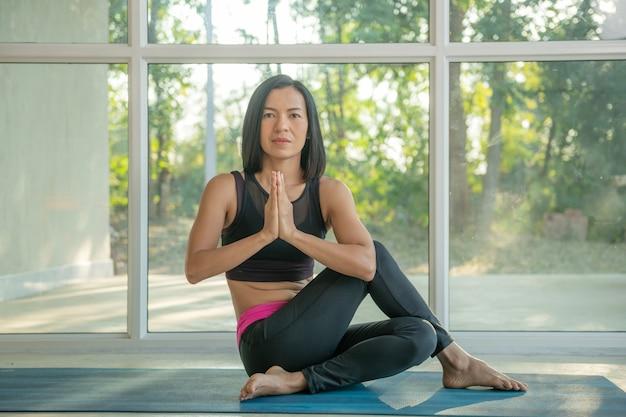 Jovem mulher atraente praticando exercícios de ioga em casa, ardha matsyendrasana pose com namaste, malhando, vestindo roupas esportivas, calças e top, corpo inteiro interno, estúdio de ioga.