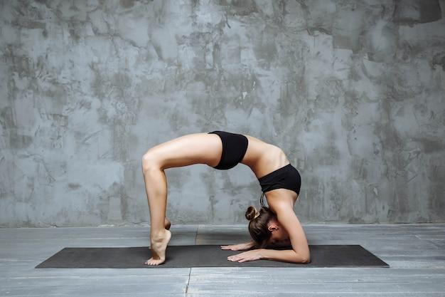 Jovem mulher atraente praticando ioga, alongamento no exercício de ponte de cotovelo