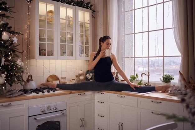 Jovem mulher atraente praticando ioga em cozinha moderna
