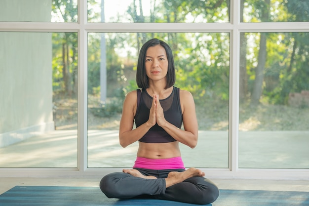 Jovem mulher atraente praticando ioga, sentada em padmasana, exercício, pose de lótus, namaste, malhando, vestindo roupas esportivas, calça preta, corpo inteiro interno, perto da janela do chão.