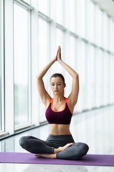 Jovem mulher atraente praticando ioga, sentada em padmasana, exercício, pose de lótus, namaste, malhando, vestindo roupas esportivas perto da janela do chão com vista para a cidade