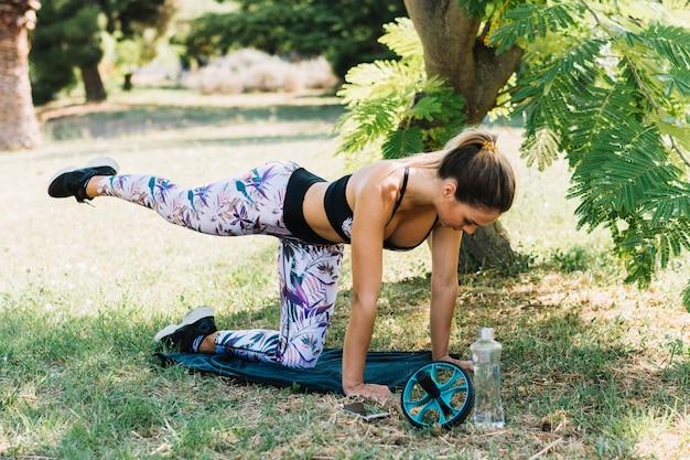 Jovem mulher atraente praticando yoga no jardim