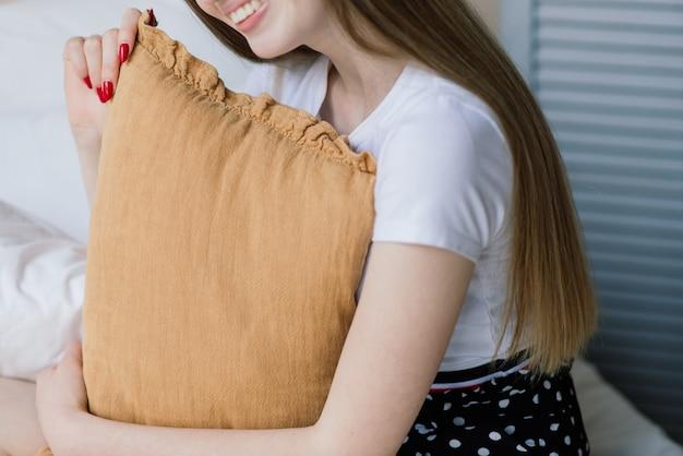 Jovem mulher atraente relaxando em um sofá branco na janela em casa