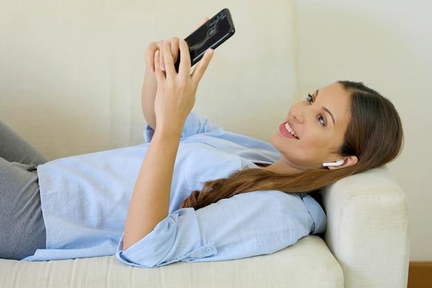 Jovem mulher atraente relaxando no sofá em casa escolhendo música no smartphone ouvindo música com fones de ouvido sem fio