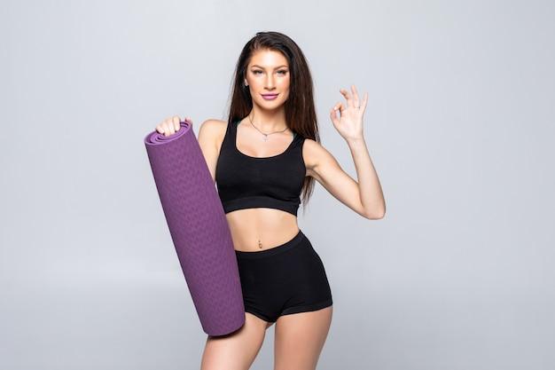Jovem mulher atraente, segurando um tapete de ioga isolado